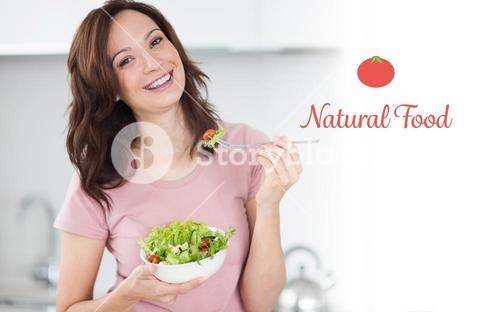 Natural food against portrait of smiling woman with a bowl of salad in kitchen