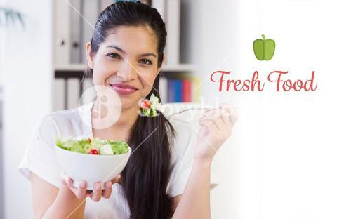 Fresh food against businesswoman eating salad in office