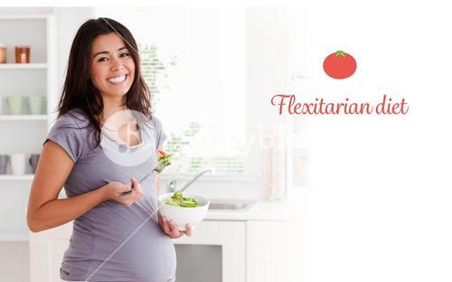 Flexitarian diet against attractive pregnant woman holding a bowl of salad while standing