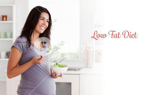 Low fat diet against beautiful pregnant woman holding a bowl of salad while standing