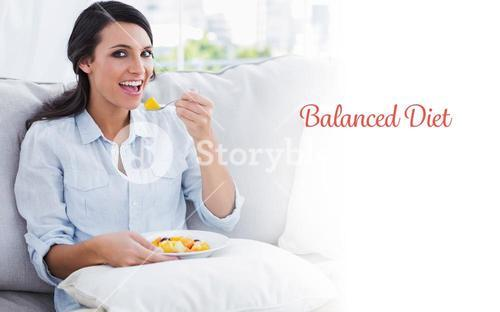 Balanced diet against happy woman sitting on the sofa eating fruit salad