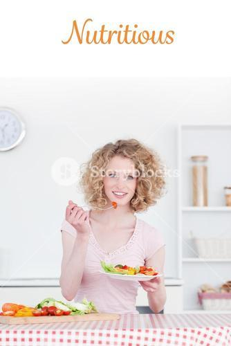 Nutritious against pretty blonde woman eating some vegetables in the kitchen