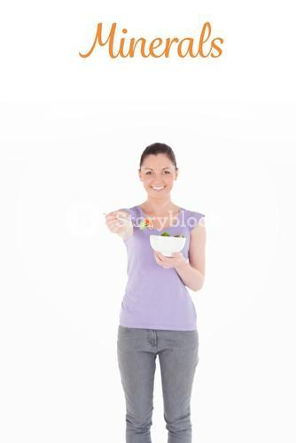 Minerals against beautiful woman holding a bowl of salad while standing