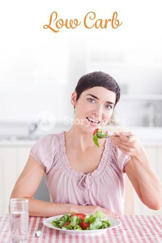 Low carb against cheerful brunette woman eating salad