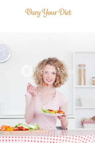 Vary your diet against pretty blonde woman eating some vegetables in the kitchen