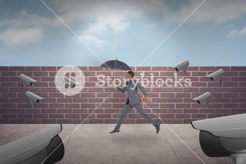 Composite image of businessman walking and holding umbrella