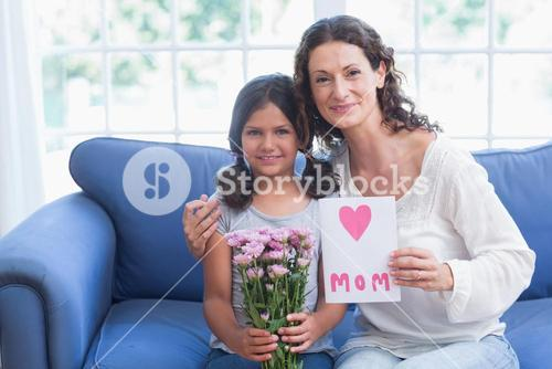 Cute girl offering flowers and card to her mother