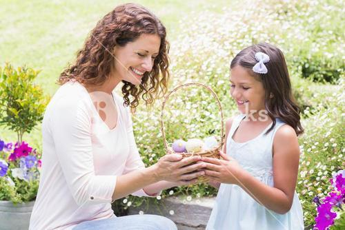 Happy mother and daughter collecting easter eggs