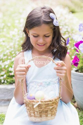 Happy girl collecting easter eggs