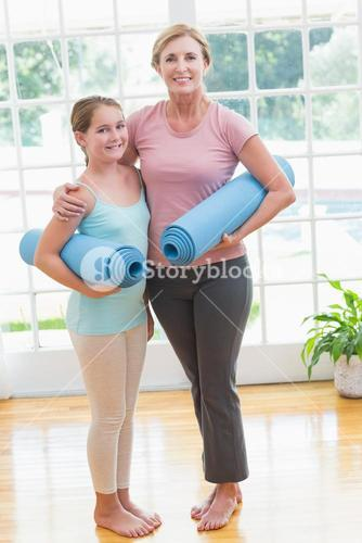 Mother and daughter holding yoga mats