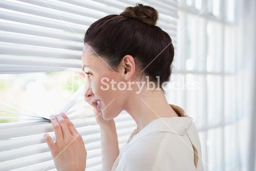 Woman peeking through the blinds