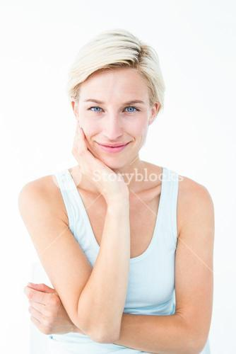 Happy woman smiling at camera with hand on cheek