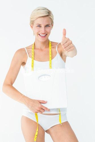 Happy woman holding scales with thumbs up