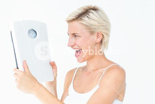 Happy blonde woman holding scales