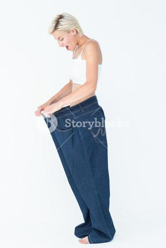 Surprised blonde wearing too large pants