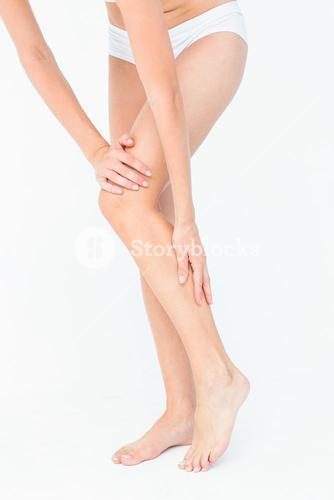 Attractive woman touching her leg