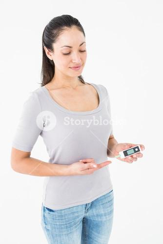 Diabetic brunette holding blood glucose monitor
