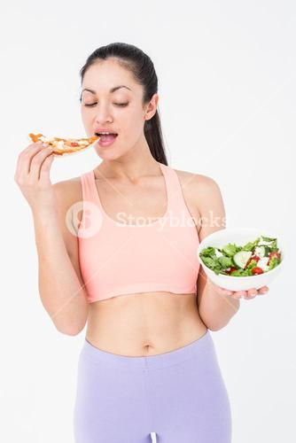 Pretty brunette eating pizza and holding salad