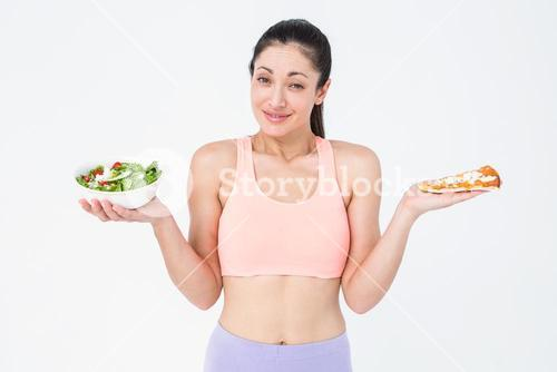Pretty brunette holding pizza and salad