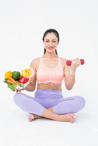 Fit brunette lifting dumbbell and holding bowl of salad
