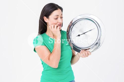Brunette looking at wall clock