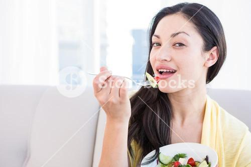 Pretty brunette looking at camera and eating vegetables