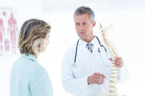 Doctor having conversation with his patient and showing spine model