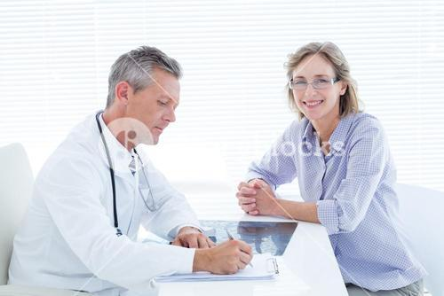 Patient smiling at camera while doctor taking notes