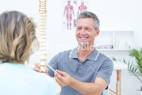 Smiling physiotherapist showing spine model to his patient