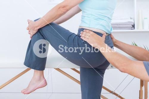 Physiotherapist examining his patient back