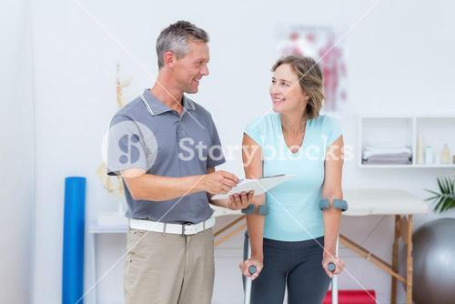 Woman using crutch and talking with her doctor