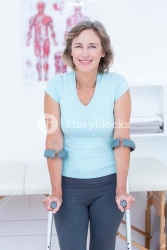 Woman standing with crutch and smiling at camera