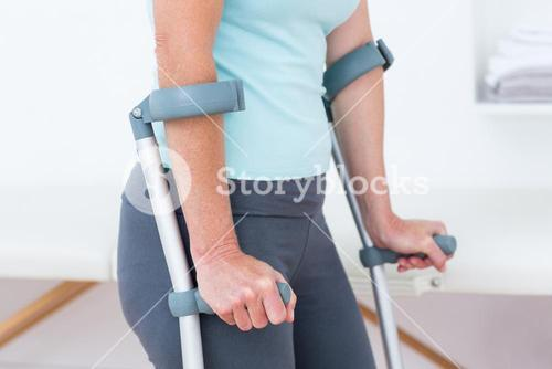 Woman standing with crutch