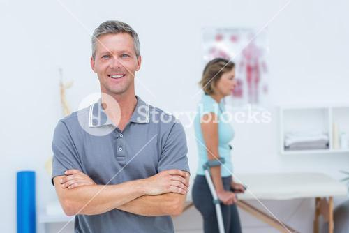 Doctor smiling at camera while his patient standing with crutch