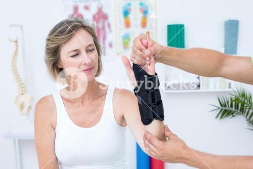 Doctor examining his patients wrist