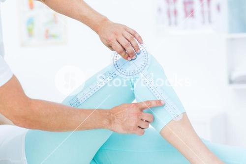 Doctor measuring knee with goniometer