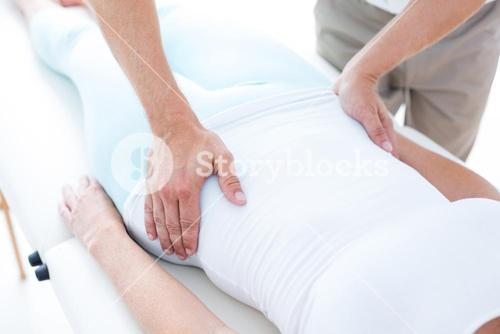 Physiotherapist examining his patients stomach