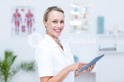 Smiling doctor using tablet