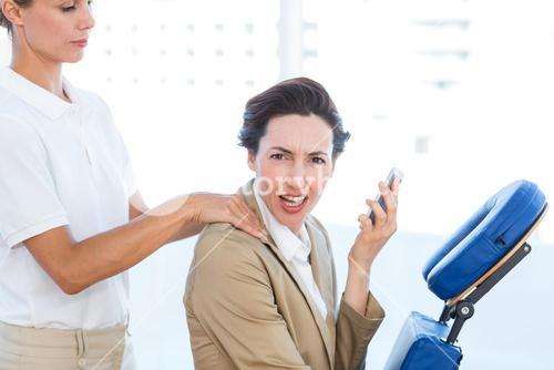 Upset businesswoman having back massage