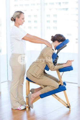 Businesswoman having back massage while using her mobile phone