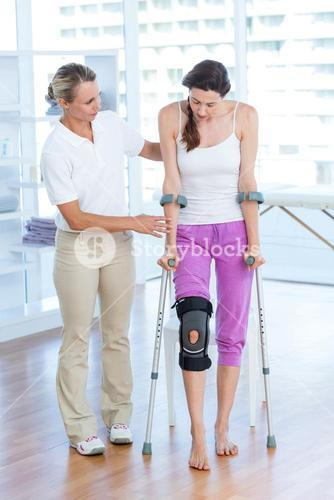 Doctor helping woman walking with crutches