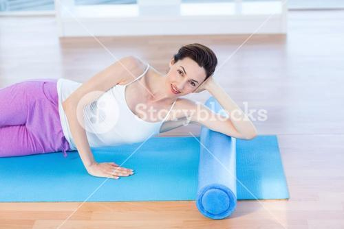 Smiling woman lying on exercise mat