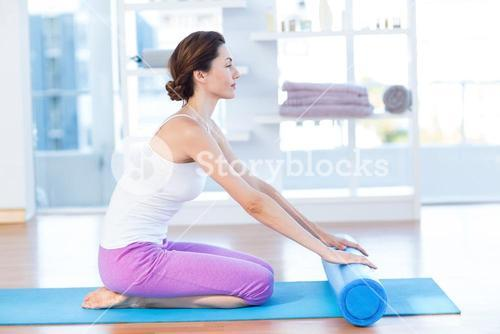 Smiling woman sitting on exercise mat