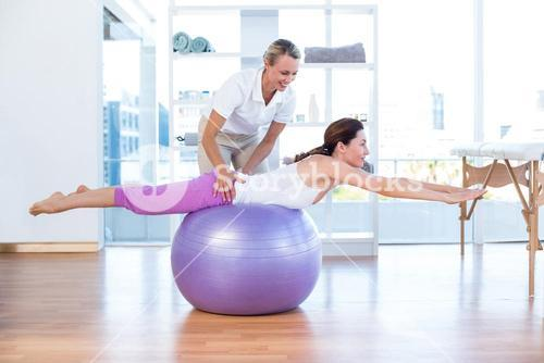 Trainer helping woman on exercise ball