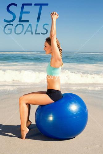Composite image of fit woman sitting on exercise ball at the beach stretching arms