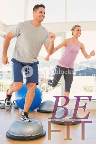 Composite image of couple doing step aerobics in fitness studio
