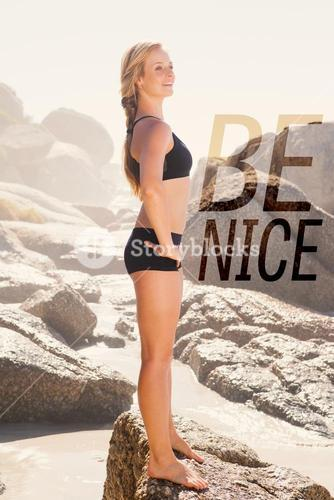 Composite image of fit blonde standing on the beach on a rock