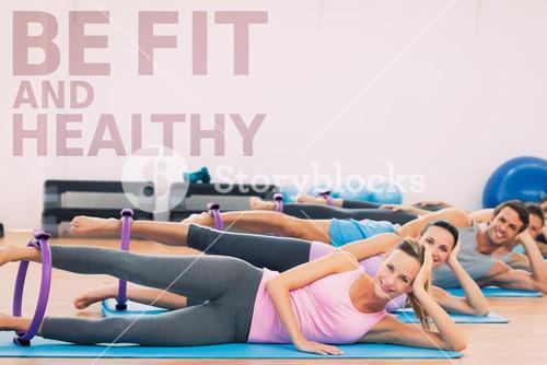 Composite image of sporty people with exercising rings in fitness studio