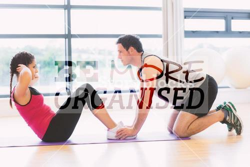 Composite image of trainer helping woman do abdominal crunches in gym