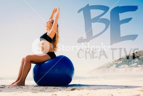 Composite image of fit blonde sitting on exercise ball at the beach